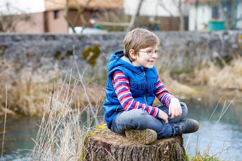 Kinderjunge mit zufälliger bunter Kleidung und Auge tragen die Gläser, die auf Baumstumpf sitzen lizenzfreie stockbilder