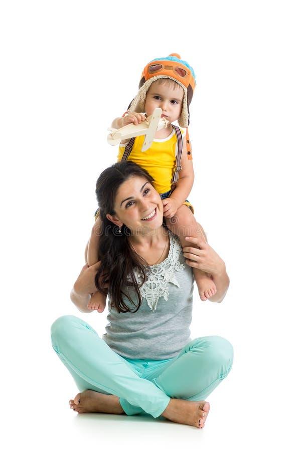 Kinderjunge spielt Versuchssitzen auf Mutterschultern lizenzfreies stockbild
