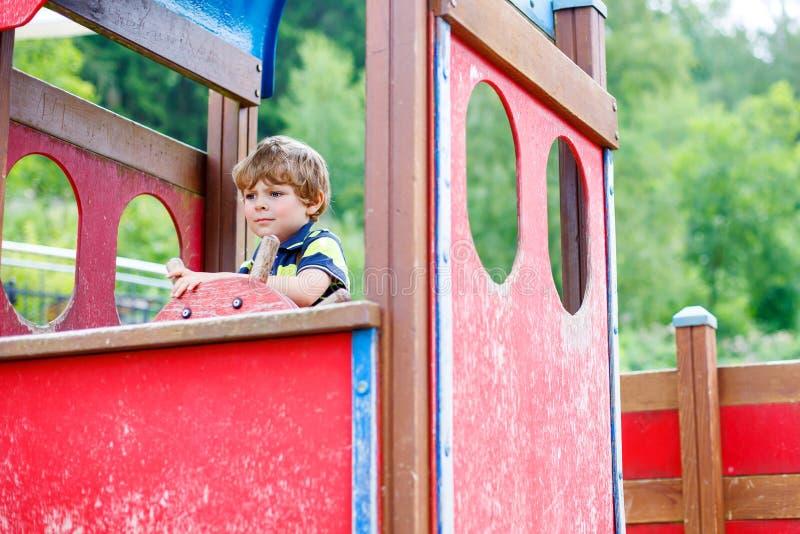 Kinderjunge täuscht das Fahren eines eingebildeten Autos auf Kinderspielplatz vor lizenzfreie stockfotografie