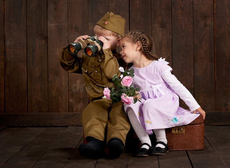 Kinderjunge werden wie Soldat in den Retro- Militäruniformen und im Mädchen im rosa Kleid gekleidet, das auf altem Koffer, dunkle lizenzfreies stockfoto