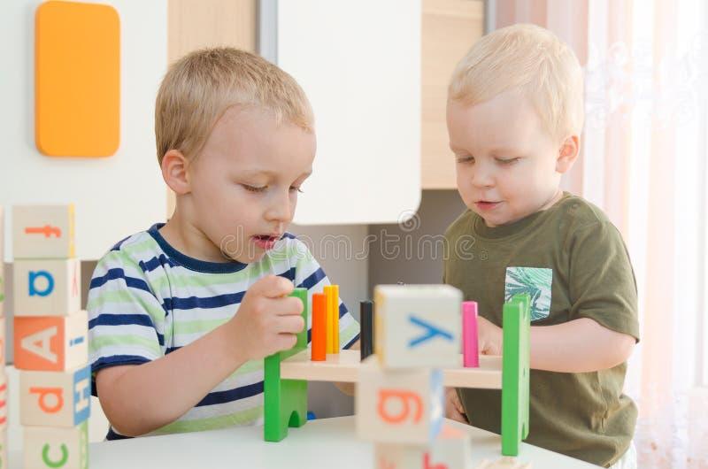 Kinderjungen, die zu Hause mit Bauklötzen oder Kindergarten spielen stockfotos