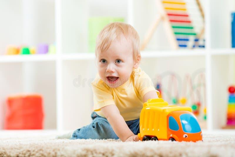 Kinderjungenkleinkind, das mit Spielzeugauto spielt stockbilder
