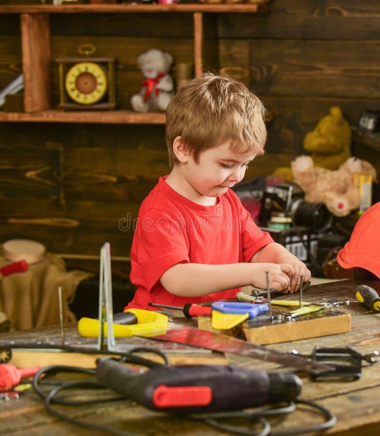 Kinderjungenspiel als Heimwerker Kindernettes und entzückendes Spielen mit Werkzeugen als Erbauer oder Reparaturhauer, Reparatur  lizenzfreie stockbilder