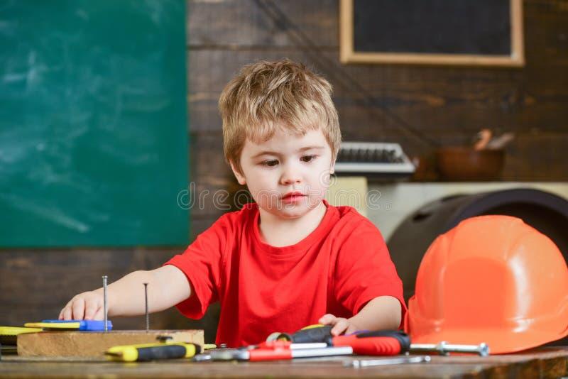 Kinderjungenspiel als Heimwerker Kindheitskonzept Kleinkind auf beschäftigtem Gesicht spielt mit Werkzeugen zu Hause in der Werks lizenzfreie stockfotos