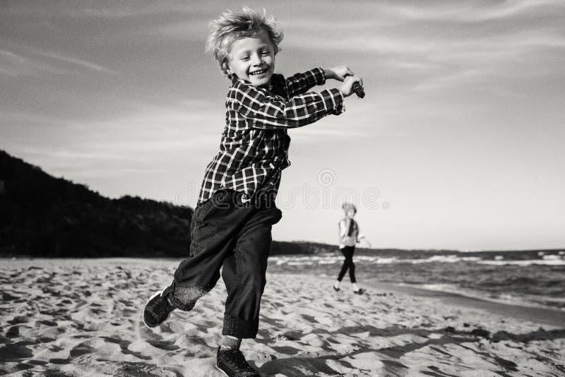 Kinderkind, das mit hölzernem Stock auf Ozeanseestrand auf Sonnenuntergang spielt stockfotografie