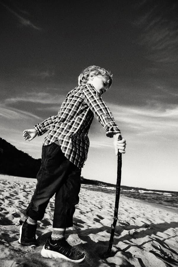 Kinderkind, das mit hölzernem Stock auf Ozeanseestrand spielt stockbild