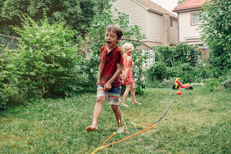 Kinderkinder, die mit Gartenarbeitschlauchberieselungsanlage auf Hinterhof am Sommertag spritzen stockbilder