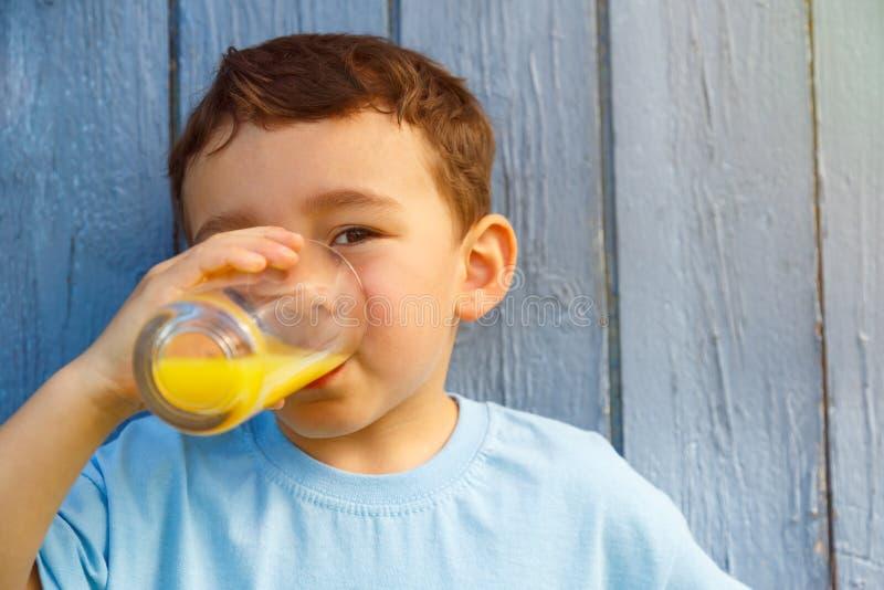 Kinderkinderkleiner Junge, der Orangensaftgetränk copyspa im Freien trinkt lizenzfreies stockfoto