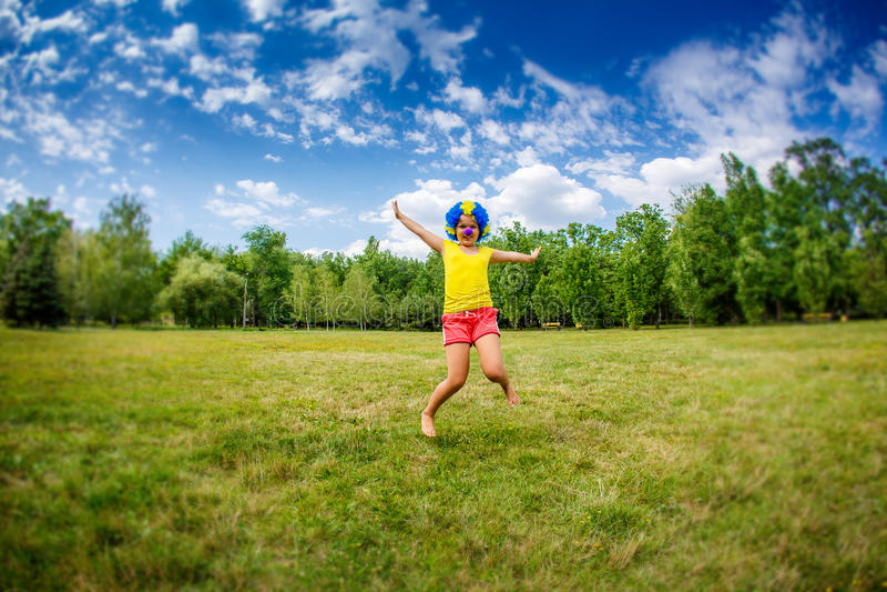 Kinderkindermädchen mit den lustigen glücklichen offenen Armen Ausdruck und Girlanden der blauen Perücke des Parteiclowns springt lizenzfreie stockfotos