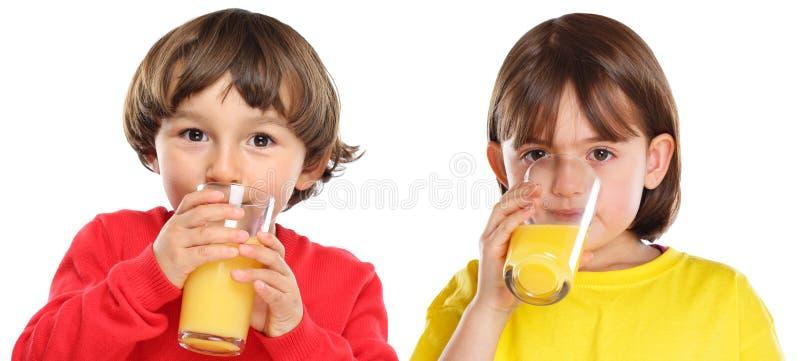 Kinderkindermädchenjunge, der die Orangensaftgesunde ernährung lokalisiert auf Weiß trinkt stockfotos