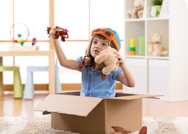Kinderkinderpilot, der eine Pappschachtel fliegt lizenzfreie stockfotos