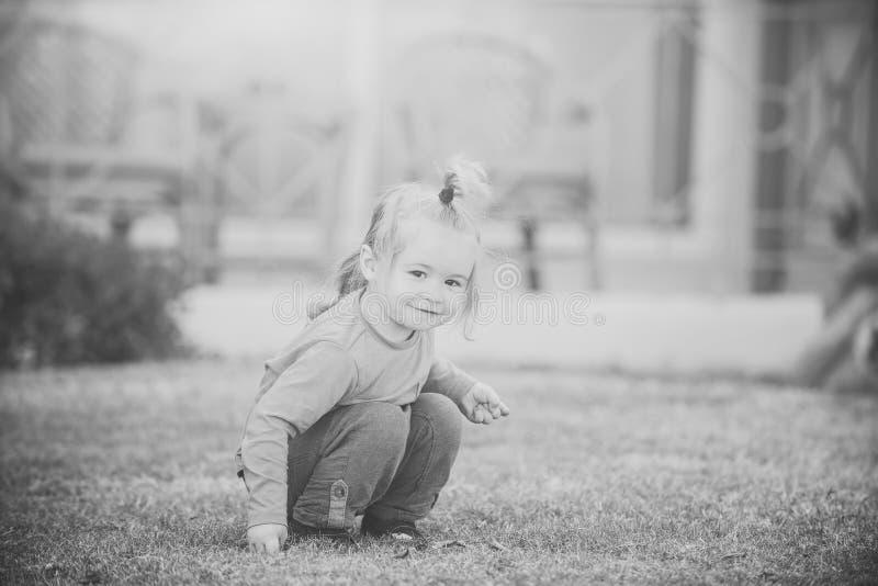 Kinderkindheits-Kinderglück-Konzept Baby, das mit Blättern spielt stockfoto