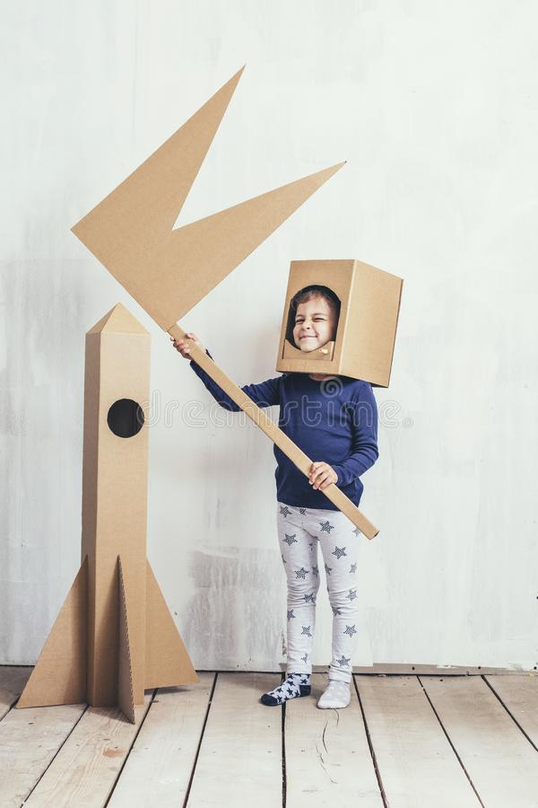 Kinderkleine Mädchen, die Raumfahrer mit einer Papprakete spielen und stockbilder