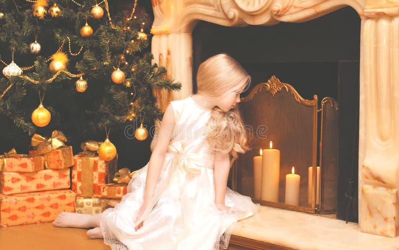 Kinderkleines Mädchen mit Geschenkkästen nähern sich Weihnachtsbaum und Kaminhaus stockbild