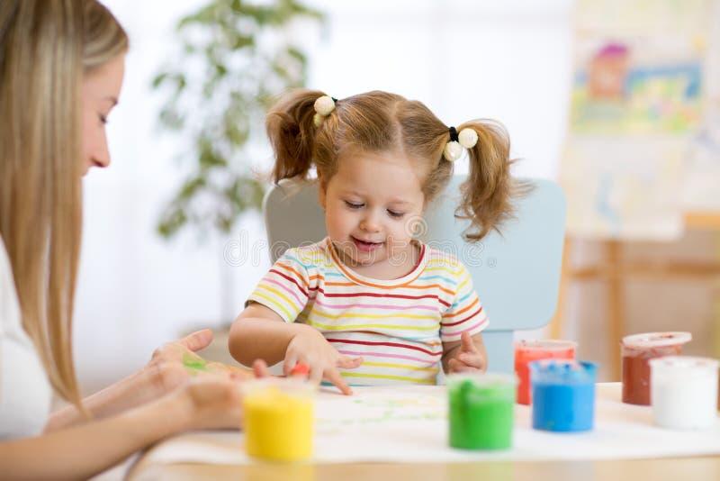Kinderkleinkindmalerei in der Kindertagesstätte zu Hause stockfotografie