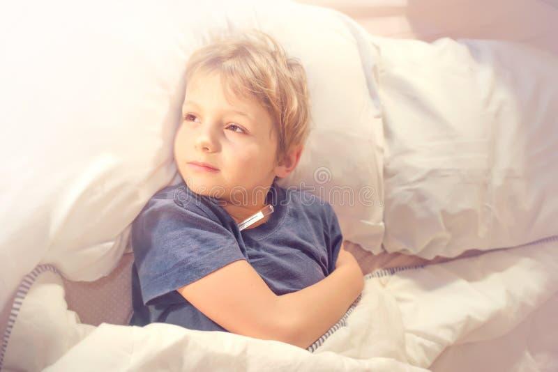 Kinderkranker im Bett mit Fieber und Thermometer lizenzfreie stockfotografie