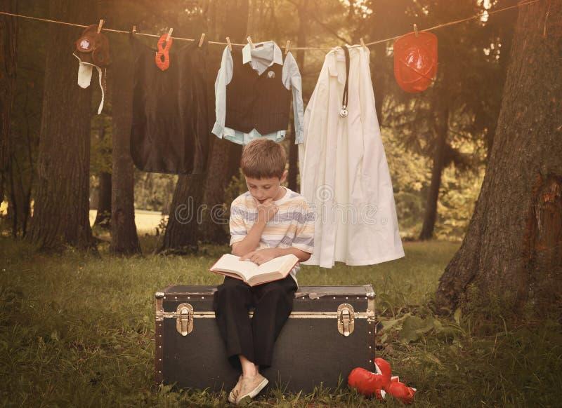 Kinderlesebuch mit dem Karriere-Uniform-Hängen stockbild