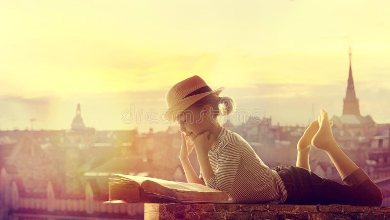 Kinderlesebuch-Stadt-Dach im Freien, glückliches Mädchen-Kind gelesen und Dr. lizenzfreie stockbilder