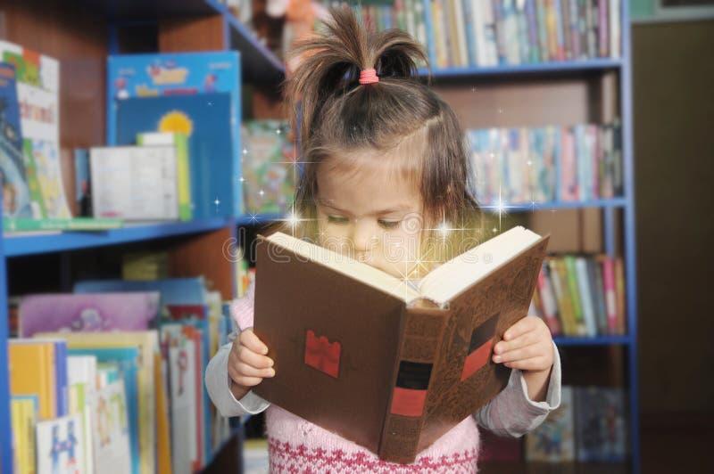 Kinderlesemagisches Buch wenig Mädchen im laibrary Untersuchung Märchen Wunder der Ausbildung lizenzfreie stockfotografie