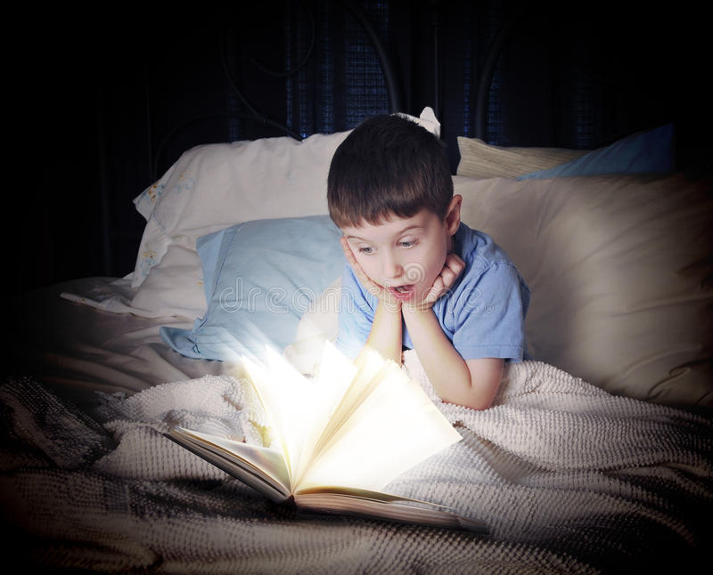 Kinderleseoffenes buch nachts im Bett stockfotos