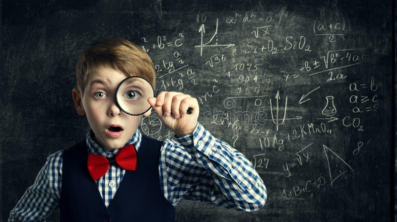 Kinderlupe, überraschtes Schulkind, Student Boy mit Magn stockfotografie