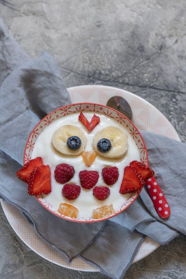 Kinderlustiger Frühstücksjoghurt mit Früchten und Beeren stockfotos