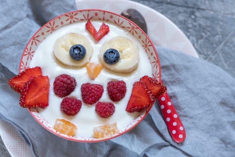 Kinderlustiger Frühstücksjoghurt mit Früchten und Beeren stockbilder