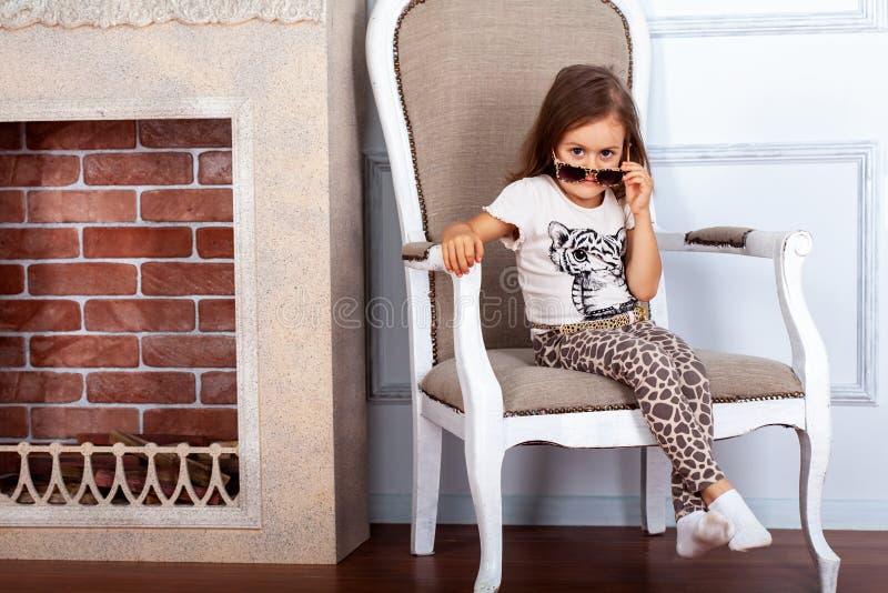 Kindermädchen, das auf einem Stuhl nahe Kamin sitzt stockfoto