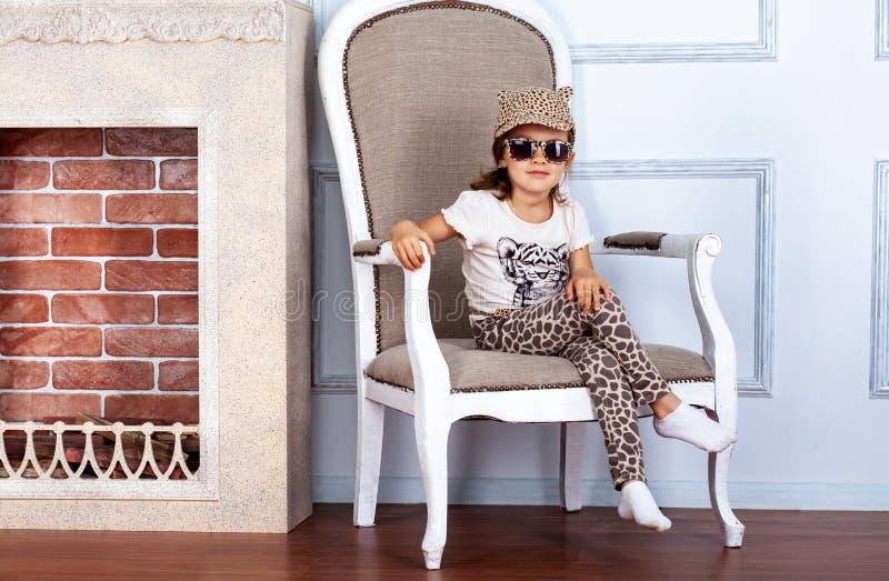 Kindermädchen, das auf einem Stuhl nahe Kamin sitzt stockbild