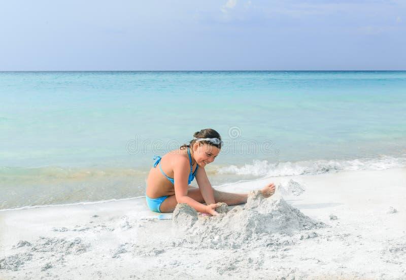 Kindermädchen, das auf herrlichem Strand des weißen Sandes nahe dem Ozean spielt lizenzfreie stockfotografie