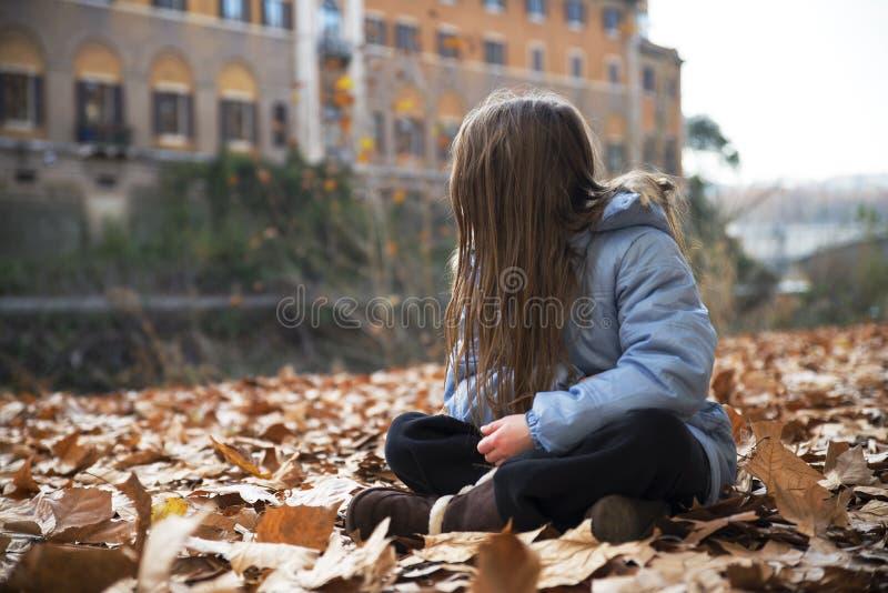 Kindermädchen, das auf sonnigem Herbstflußufer sitzt stockbilder