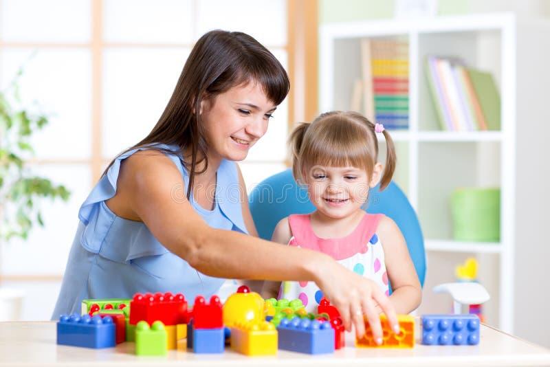 Kindermädchen, das den Bau eingestellt mit Mutter spielt lizenzfreie stockfotos