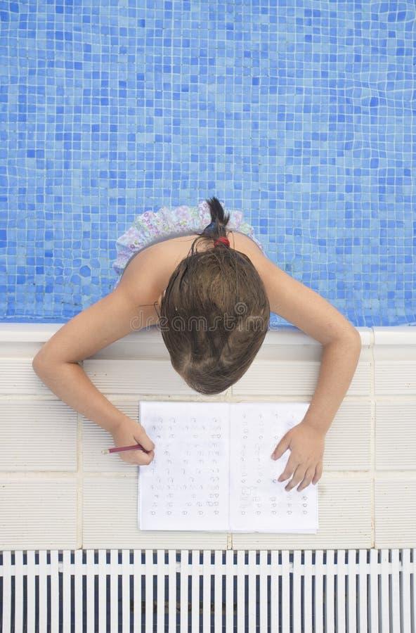 Kindermädchen, das Feiertagshausarbeit über Schwimmen Poolside tut stockfotos