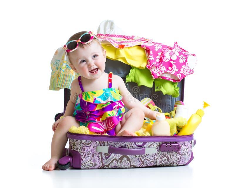 Kindermädchen, das im Koffer mit Sachen für sitzt stockfotos
