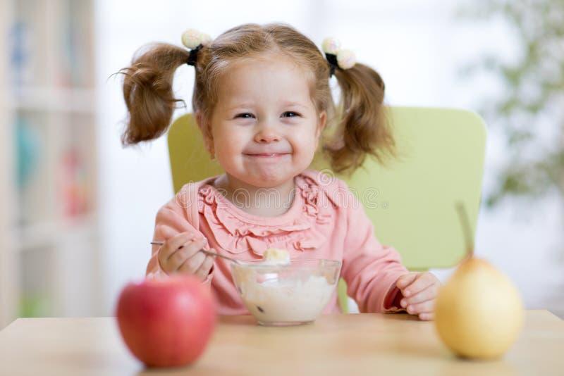 Kindermädchen, das mit Löffel isst stockfotografie