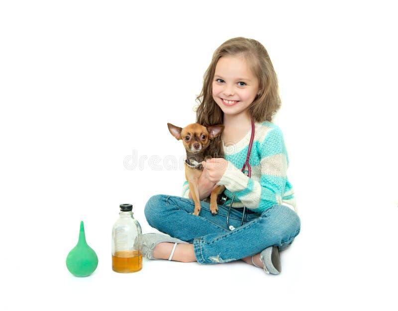 Kindermädchen, das Tierarzt mit ihrem kleinen Hund spielt lizenzfreie stockfotografie