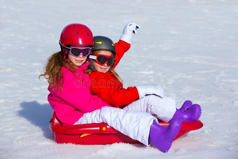 Kindermädchen, die Schlitten im Winterschnee spielen lizenzfreies stockfoto
