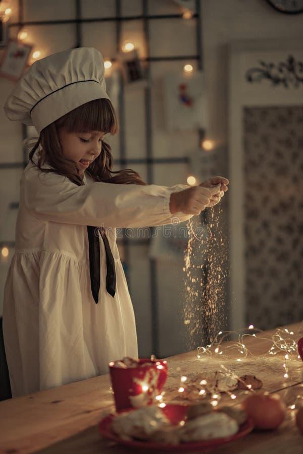Kindermädchen in einer Kochkappe besprüht Mehl auf dem Tisch stockfoto