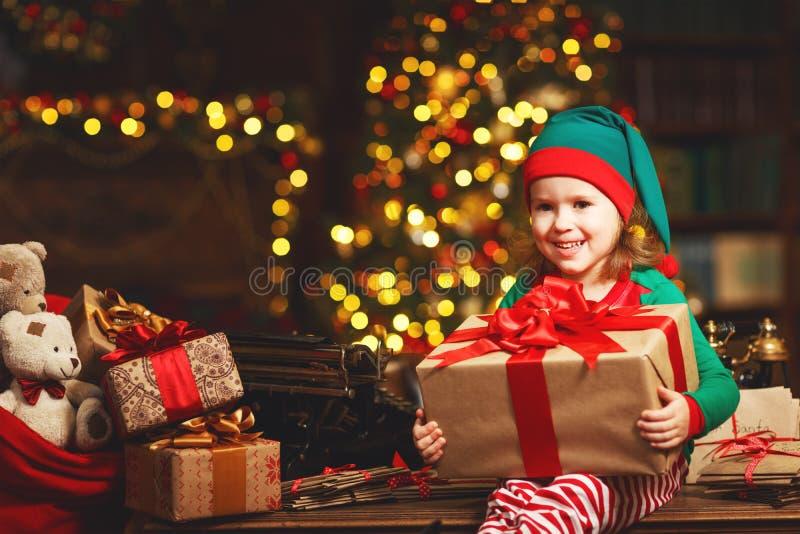 Kindermädchen-Elfenhelfer von Sankt mit einem Weihnachtsgeschenk stockbild