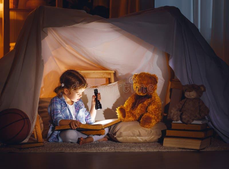 Kindermädchen mit einem Buch und eine Taschenlampe und Teddybär vor gehen lizenzfreie stockbilder