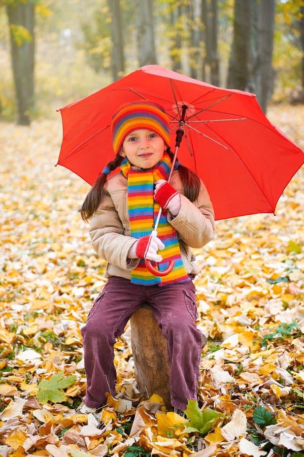 Kindermädchen sitzen auf Stamm mit rotem Regenschirm im Herbstwald, gefallene Blätter auf Hintergrund, Herbstsaison lizenzfreies stockfoto