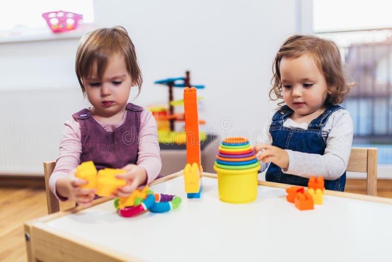 Kindermädchen spielen Spielwaren zu Hause, Kindergarten oder Kindertagesstätte stockbilder