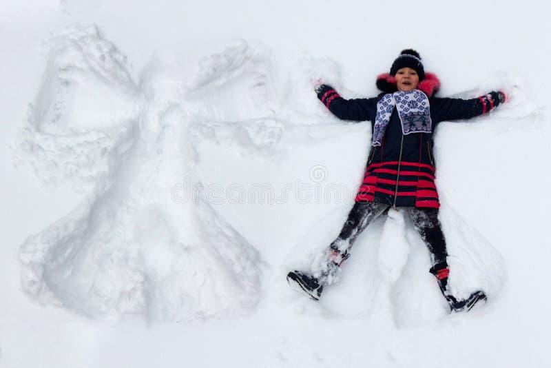 Kindermädchen spielt im Schnee und macht einen Schneegel lizenzfreies stockbild