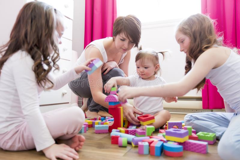 Kindermädchen zusammen mit der Mutter und Schwester, die pädagogische Spielwaren spielen lizenzfreie stockfotografie