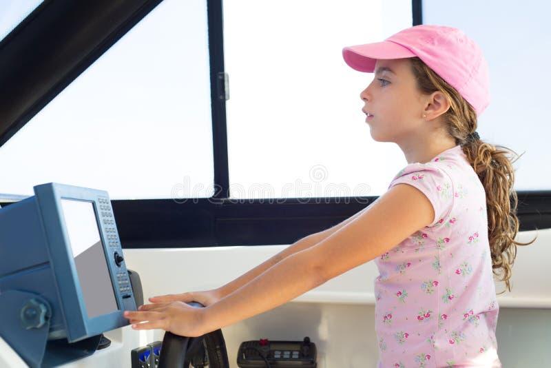 Kindermädchensegeln, welches das Bootsrad steuert lizenzfreies stockbild