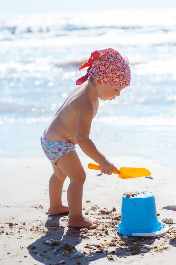 Kindermädchenspiel auf einem Strand Kindergebäudesandburg auf Strand Sommerwasserspa? f?r Familie Mädchen mit Spielzeugeimern und stockfotos