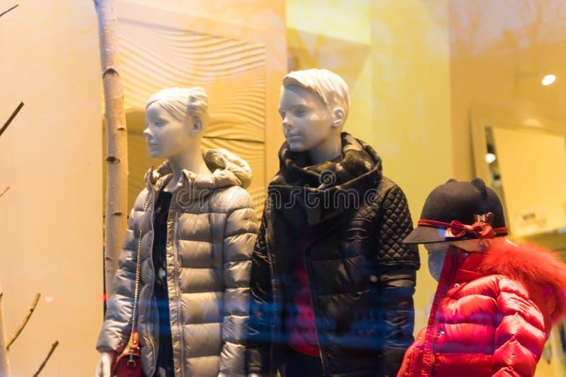 Kindermannequins in der warmen Kleidung in einem Shopfenster stockbild