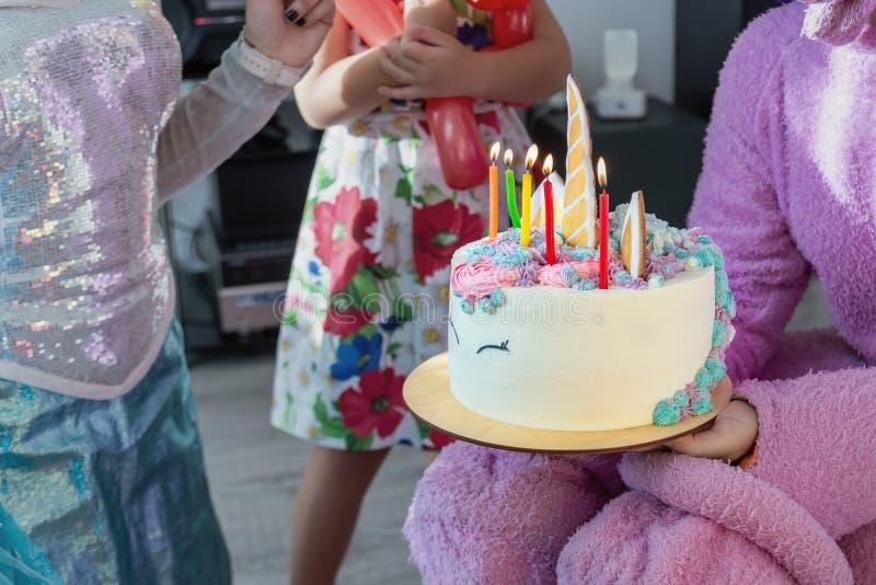 Kinderparteientertainer gibt den geschmackvollen hellen Kuchen, der in der Form des Fantasieeinhorns für das Kind verziert wird,  lizenzfreie stockbilder