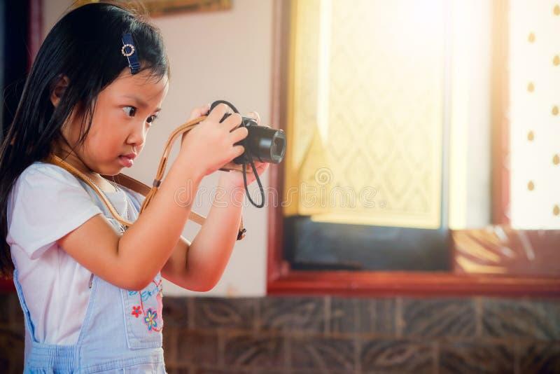 Kinderphotograph, glückliche haltene Kamera des asiatischen Mädchens stockfoto