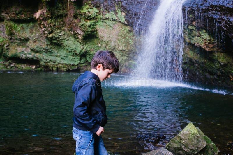Kinderporträt vor einem Wasserfall und einer Lagune im Wald lizenzfreie stockbilder